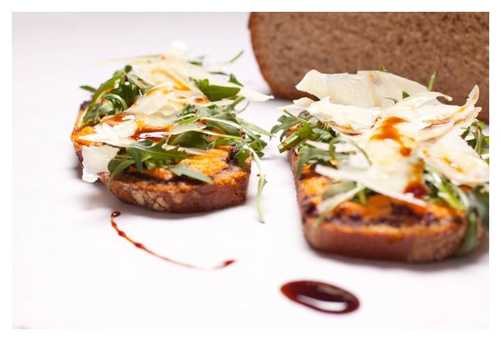 Tosta con paté de aceitunas de kalamata, salsa fresca de tomate, lascas de parmigiano-reggiano y reducción de PedroXiménez